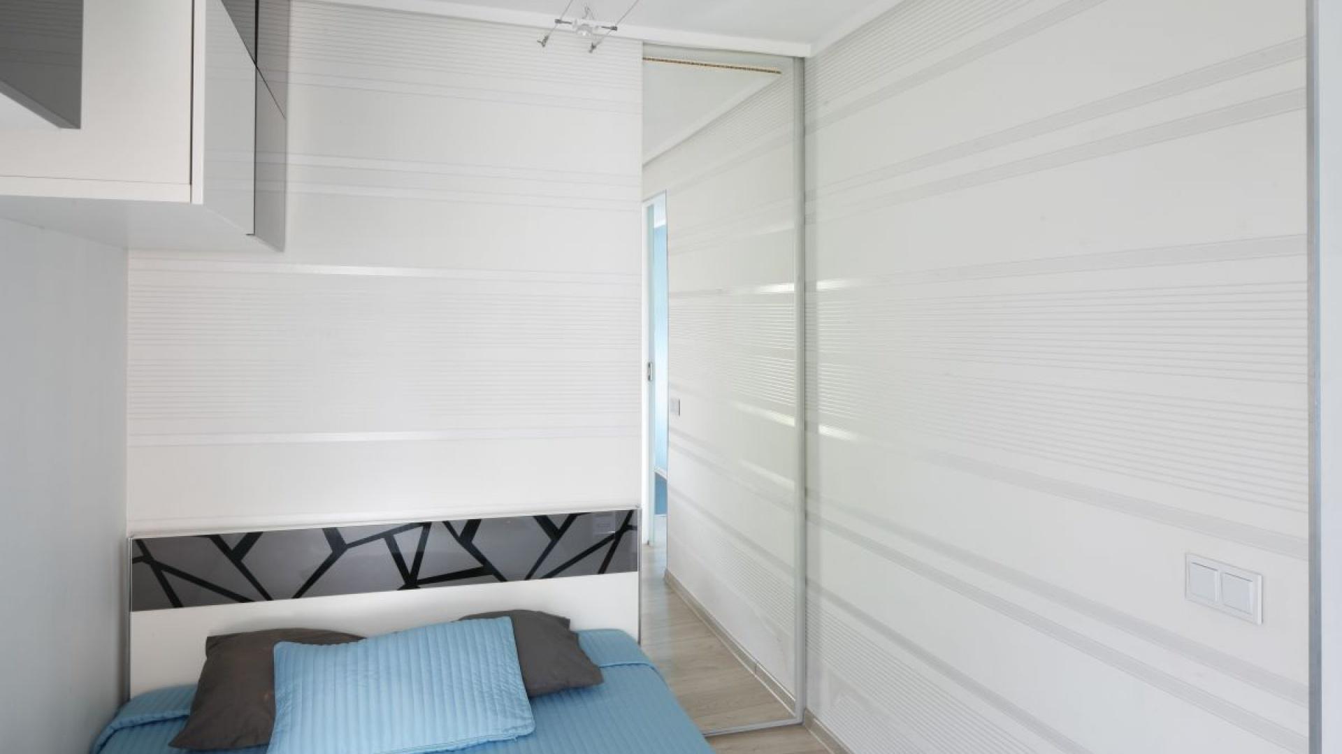 W sypialni połączono trzy kolory: biel, czerń oraz turkus. Połyskujące fronty szafek oraz dekoracyjna tapeta w poziome pasy optycznie powiększają przestrzeń. Lustrzana tafla drzwi przesuwnych prowadzących do niewielkiej garderoby także dodaje wnętrzu przestronności. Fot. Bartosz Jarosz.