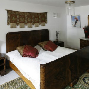 Ciemne, masywne formy mebli kontrastują z jasnymi ścianami. Tradycyjne tkaniny: dywan, poduszki dekoracyjne, ozdoba nad łóżkiem ocieplają wnętrze sypialni. Fot. Archwium Dobrze Mieszkaj.