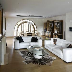 Pomieszczenie podzielono na dwie strefy: jadalnianą i wypoczynkową. Granicę tej drugiej przestrzeni wyznaczają dwie sofy, ustawione w kształt litery L. Fot. Bartosz Jarosz.