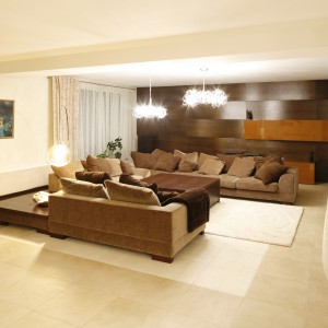 Przestronny salon w kolorze ecru ocieplają wygodne, długie sofy o barwie ciepłego brązu. Koresponduje z nimi ściana wyłożona panelami. Fot. Bartosz Jarosz.