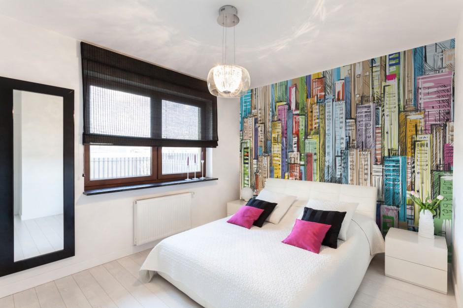 Dekoracyjna fototapeta przedstawiająca rysunek kolorowych, wysokich budynków. Dynamiczny szkic przeniesiony na ścianę za łóżkiem tworzy ciekawą dekorację sypialni. Fot. Minka.