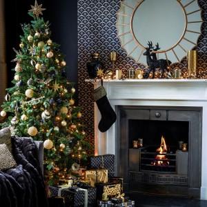W tej szykownej, eleganckiej dekoracji domu na Święta, czarna figurka renifera dumnie stoi nad kominkiem. Dekoracja harmonizuje z czarną skarpetą na prezenty i wpisuje się w ciemną kolorystykę ścian. Fot. House of Fraser.