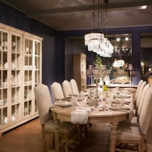 Szykowna dekoracja stołu to propozycja belgijskiej firmy Flamant. Biała porcelanowa zastawa i szklane kieliszki tworzą klasyczny duet, który idealnie sprawdzi się na sylwestrowe czy karnawałowe przyjęcie. Srebrny świecznik i futrzany bieżnik dodają aranżacji przepychu. Fot. Flamant.
