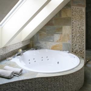 Nieodzownym elementem wyposażenia łazienki w stylu domowego SPA jest wanna z hydromasażem. Obudowa wykonana z kamiennej mozaiki pozostawia także sporo miejsca na ręczniki, kosmetyki, świece. Projekt: Karolina Łuczyńska. Fot. Bartosz Jarosz.