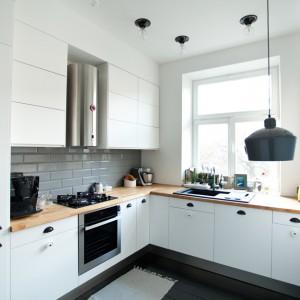 Biała kuchnia nawiązuje stylem do wnętrz skandynawskich. Drewniany blat kuchenny estetycznie przełamuje dominujące we wnętrzu zimne barwy. Estetycznym akcentem nadającym charakter umeblowaniu są czarne uchwyty, efektownie kontrastujące z frontami dolnych szafek. Projekt: Magdalena Ilmer, Boho Studio. Fot. Boho Studio.