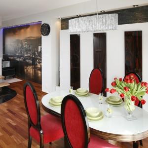 Nad stołem jadalnianym zawieszono efektowny, dekoracyjny żyrandol, pokryty licznymi połyskującymi kryształkami. Projekt: Jolanta Kwilman. Fot. Bartosz Jarosz.