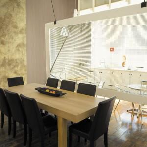 Pionowy pas złotej tapety poprowadzony wzdłuż ściany w jadalni rozświetla przestrzeń i komponuje się z drewnianą podłogą i stołem. Fot. Eksim, kolekcja Alta Gamma Vision.
