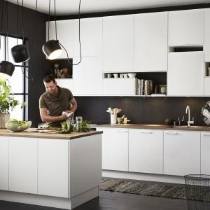 Nowoczesne białe meble kuchenne efektownie prezentują się na tle czarnej ściany i w zestawie z technicznym oświetleniem nad półwyspem. Górnym szafkom nadano oryginalny kształt, z asymetrycznymi wnękami na półki i gładkimi frontami. Fot. Ballingslov.