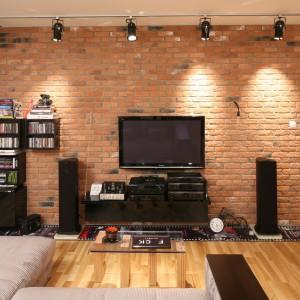 W przestronnym salonie ścianę z telewizorem wyłożono czerwoną cegłą. O jej ważkości dodatkowo przesądza fabryczne oświetlenie zamontowane na całej linii sufitu. Projekt: Iza Szewc. Fot. Bartosz Jarosz.