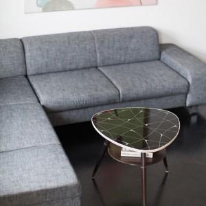 W salonie funkcję kompletu wypoczynkowego pełni praktyczny narożnik. Towarzyszy mu oryginalny stolik kawowy. Projekt: Magdalena Ilmer, Boho Studio. Fot. Boho Studio.