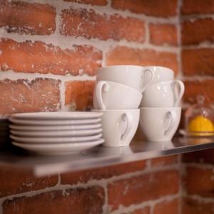 Ścianę nad blatem w kuchni wykończono okładziną, imitująca naturalną cegłę. Projekt: Magdalena Ilmer, Boho Studio. Fot. Boho Studio.