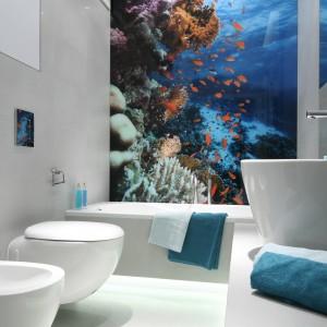 W łazience urządzonej w bieli rolę dekoracji, a także głównego elementu aranżacji pełni fototapeta.  Widok morskich głębin z kolorowymi elementami podwodnego krajobrazu stawia, że wnętrze jest kolorowe, atrakcyjne i niepowtarzalne. Projekt: Anna Maria Sokołowska. Fot. Bartosz Jarosz.