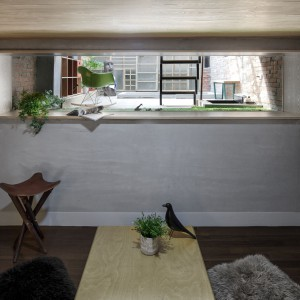 Pomiędzy pierwszym a drugim piętrem znajduje się niewielka pośrednia kondygnacja. Zlokalizowano tam pokój do relaksu Zen, z widokiem na taras z ogrodem. Przez powstałą po wyburzeniu ściany wnękę, do wnętrza wpada naturalne światło. Projekt: HAO Design Studio. Fot. Joey Liu.
