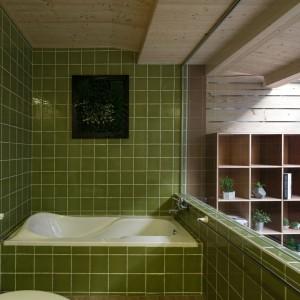 Łazienkę z widokiem na taras wykończono w kolorze zgniłej zieleni. Naturalna barwa koresponduje z materiałem użytym na suficie pomieszczenia oraz z widokiem za przeszkleniem. Projekt: HAO Design Studio. Fot. Joey Liu.
