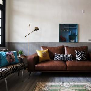 Tapicerowana, skórzana kanapa pięknie harmonizuje z drewnem na podłodze i ścianie. Naturalną kolorystykę przełamano ciemnym błękitem w postaci poduszki dekoracyjnej i niewielkiej, asymetrycznej szafki wiszącej na ścianie. Projekt: HAO Design Studio. Fot. Joey Liu.