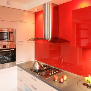 Czerwone szafki wiszące stanowią jedynie niewielką część zabudowy. Aby zaznaczyć ich obecność ścianę, na której je umocowano, wykończono tym samym kolorem. Projekt: Marta Kruk. Fot. Bartosz Jarosz.