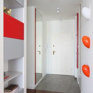 Strefę wejścia optycznie powiększa również biel. W duecie z czerwienią tworzy ona lejtmotyw całej aranżacji. Projekt: Iza Szewc. Fot. Bartosz Jarosz.