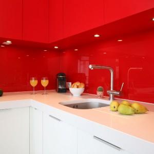 Intensywna czerwień górnych szafek przechodzi w szklaną ścianę nad blatem. Jednolita kolorystyka obu powierzchni efektownie kontrastuje z bielą blatu i dolnych szafek. Projekt: Iza Szewc. Fot. Bartosz Jarosz.