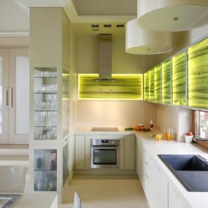 W tej kuchni elementem wprowadzającym kolor do wnętrza są szklane fronty wiszących szafek. Efektownie podświetlona soczysta zieleń z motywem roślinnym pięknie ożywia przestrzeń kuchni. Projekt: Małgorzata Borzyszkowska. Fot. Bartosz Jarosz.