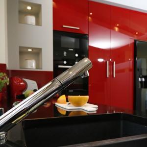 Na tle czerwonej, wysokiej zabudowy efektownie wyeksponowano sprzęty kuchenne, które zachwycają połyskującą czernią. Czarny i połyskujący jest także blat kuchenny. Projekt: Jolanta Kwilman. Fot. Bartosz Jarosz.
