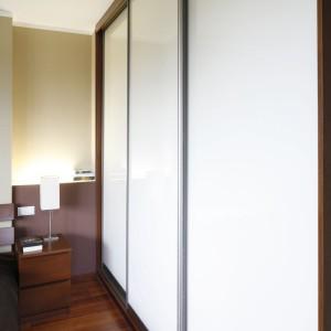 Wysoka zabudowa zapewnia wiele miejsca na przechowywanie. Białe fronty nie przytłaczają wnętrza a przesuwny system zapewnia oszczędność miejsca i wygodne użytkowanie. Fot. Bartosz Jarosz.