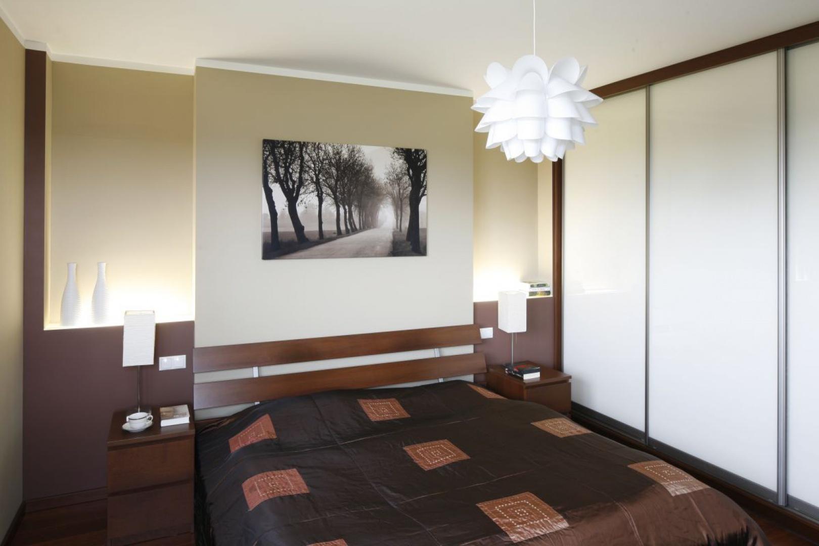 Sypialnia została urządzona bardzo funkcjonalnie. Wygodne łóżko, praktyczne stoliki nocne, pojemna zabudowa, spójne oświetlenie oraz spokojna kolorystyka tworzą ponadczasowe wnętrze. Fot. Bartosz Jarosz.