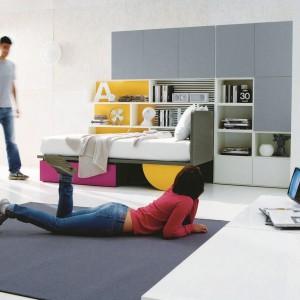 W minimalistycznym pokoju meble ograniczono do minimum. Praktyczna zabudowa i kolorowe łóżko z pojemną szufladą organizują przestrzeń, dzięki czemu we wnętrzu panuje ład i porządek, Fot. Dielle.