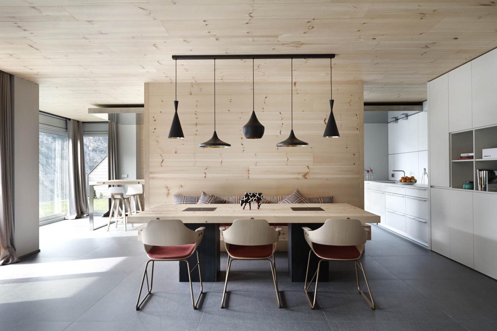 Efektowne krzesła i lampy stanowią przykuwający wzrok element dekoracyjny, pięknie wyeksponowany na tle prostej, drewnianej powierzchni. Projekt: Coblonal Arquitectura. Fot. Sara Riera.