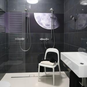 Przestrzeń łazienki jest otwarta, nie ma tutaj zasadniczych podziałów; nawet  strefa prysznica nie jest oddzielona od reszty pomieszczenia. Panek dekoracyjny ze zdjęciem przeskalowanego księżyca stanowi wyjątkową dekoracje. Projekt: Kasia i Michał Dudko. Fot. Bartosz Jarosz.