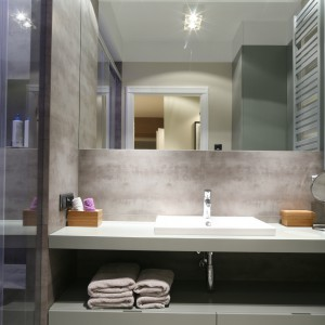 Nieco przestrzeni dodaje łazience spore lustro zamontowane nad umywalką. Pod blatem mieści się praktyczna wnęka, w której można ukryć ręczniki i inne drobiazgi.  Projekt: Lucyna Kołodziejska. Fot. Bartosz Jarosz.