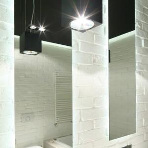 Cegła, którą wykończono wszystkie ściany łazienki, oraz zimna barwa oświetlenia budują chłodną atmosferę. Pozbawione ram lustra, kubistyczne kształty armatury to charakterystyczne elementy stylu loft. Projekt: Dominik Respondek. Fot. Bartosz Jarosz.