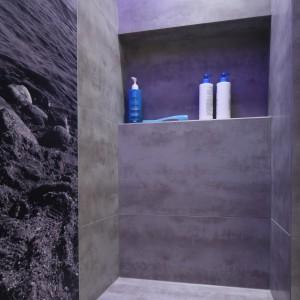 Dodatkowy efekt daje błękitne światło sączące się z linii świetlnej umieszczonej przy suficie. Pozostałe ściany wykończone zostały szarymi płytkami. Projekt: Lucyna Kołodziejska. Fot. Bartosz Jarosz.
