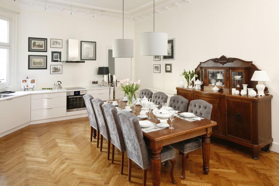 Meble kuchenne uzupełnia solidny drewniany stół na zdobionych nogach oraz drewniana, stylizowana komoda. Projekt: Iwona Kurkowska. Fot. Bartosz Jarosz.