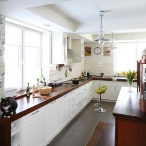 Ścianę w tej kuchni zdobią nie tylko tradycyjne, białe kafle ale również kwiecista tapeta. Przywodzi na myśl babciną kuchnię i stwarza domowy klimat we wnętrzu. Projekt: Magdalena Misiaczek. Fot. Bartosz Jarosz.