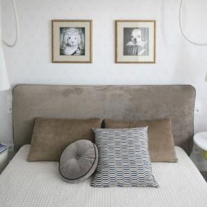 Tapicerowane wezgłowie łóżka nawiązuje kolorystyką do wykładziny. W sypialni zdecydowano się na dekoracyjne poduszki o zróżnicowanych kolorach i kształtach, dzięki czemu wnętrze nabiera charakteru. Projekt: Katarzyna Dudko, Michał Dudko. Fot. Bartosz Jarosz.
