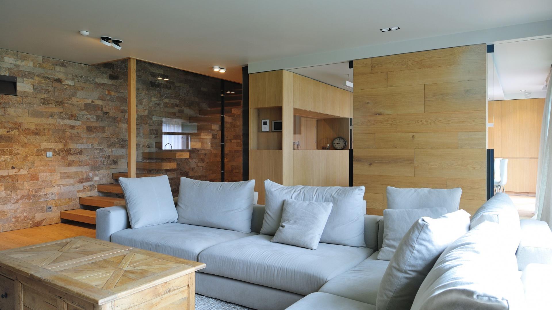 W salonie króluje bardzo duży narożnik, kolorystycznie komponujący się z miękkim dywanem na podłodze w strefie wypoczynkowej. Projekt: Coblonal Arquitectura. Fot. Coblonal Arquitectura.