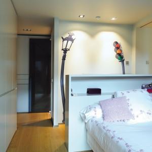 Pokój dziecięcy urządzono w bieli. Funkcję zagłówka łóżka pełni drewniany mebel z praktyczną półeczką na wygodne wysokości nad głową. Ścianę zabudowano wysoką zabudową. Projekt: Coblonal Arquitectura. Fot. Coblonal Arquitectura.