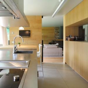 Od salonu kuchnię umownie oddziela pas zabudowy, który posłużył również za miejsce montażu telewizora. Przyrządzając posiłki można oglądać ulubiony serial. Projekt: Coblonal Arquitectura. Fot. Coblonal Arquitectura.