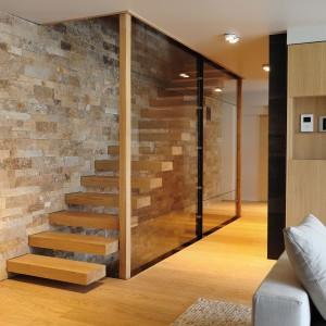 Schody wspornikowe z drewnianymi stopniami, idealnie wpasowują się w styl całego wnętrza. Wrażenie lewitowania pojedynczych stopni wzmaga szklana ścianka, zamykająca klatkę schodową. Projekt: Coblonal Arquitectura. Fot. Coblonal Arquitectura.