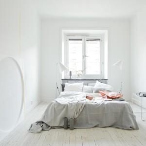 Białe, wysokie lampy podłogowe umieszczone po obu stronach łóżka stają się prawie niewidoczne na tle białych ścian. Fot. Fantasik Frank.