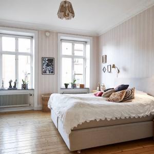 Oryginalna lampa sufitowa kolorystycznie współgra z kinkietami umieszczonymi symetrycznie po obu stronach łóżka. Fot. Stadshem.