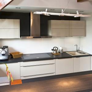 Minimalistyczna forma mebli z oferty sklepu Max-Fliz nie przytłacza wnętrza, dlatego idealnie sprawdzi się w niewielkiej kuchni. Elegancji dodaje grafitowy blat roboczy oraz stalowy okap. Fot. Max-Fliz.