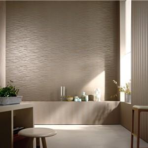 Elegancka tapeta Cuvée Prestige marki Marburger Tapetenfabrik to propozycja do wnętrz w stylu glamour. Subtelny wzór przypominający delikatne ruchy tafli wody uwypuklono perłowym wykończeniem papieru. Fot. Marburger Tapetenfabrik.