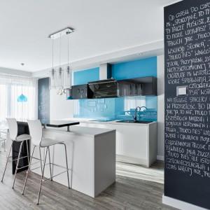 Biała wyspa kuchenna urozmaicona została elementami w czarnym kolorze, w wysokim połysku. Dwa hokery i podniesiony blat czynią z niej idealny domowy bar. Fot. Atlas kuchnie, kuchnia Patrycja.