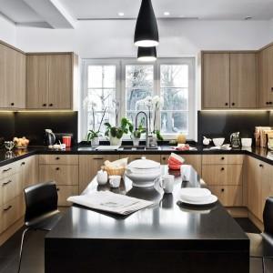 Ciepła, rodzinna kuchnia w delikatnie klasycyzującym stylu. Fronty pokryto fornirem naturalnego dębu, blat wykonano z konglomeratu kwarcowego w czarnym kolorze. Czarne są także ozdobne uchwyty wieńczące drzwiczki. Fot. Zajc Kuchnie, kuchnia Z5/021.