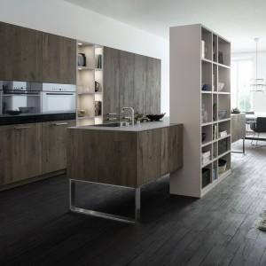 Dekor pięknego, ciemnego drewna nadaje nowoczesnym formom wytrawności i ociepla ich zimne, minimalistyczne kształty. Wyspa na metalowych nogach wygląda przytulniej, ubrana w ciepły dekor. Fot. Leicht, kuchnia Classic-fs.