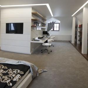 Sypialnia dorosłych domowników przechodzi płynnie w gabinet i okazałą biblioteczkę. Gabinet zlokalizowano na zabudowie, która posłużyła także za panel do instalacji TV. Projekt: Marta Pala-Szczerbak. Fot. Piotr Lipiecki.
