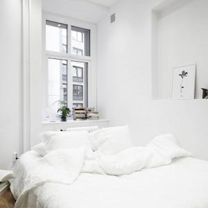 Sypialnia to królestwo bieli, ocieplonej delikatnie przez drewnianą podłogę. Parapet przy oknie i wnęka w ścianie pełnią funkcję praktycznych półek. Fot. Stadshem.se.