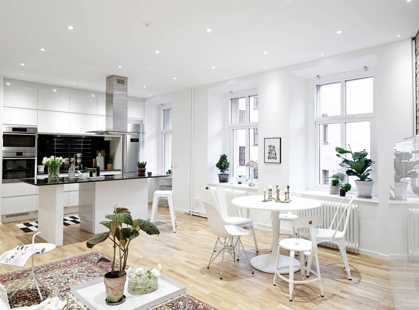Strefę dzienną tworzy salon, niewielka jadalnia oraz kuchnia, złożona z jednorzędowej zabudowy i eleganckiego półwyspu. Fot. Stadshem.se.
