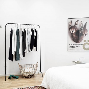 Dodatki i akcesoria pełnią istotną rolę w aranżacji tego mieszkania. Wyeksponowane na tle białych ścian, wprowadzają charakter do sterylnego wnętrza. Obrazek z sympatycznymi zającami ociepla białą sypialnię, a prosty mebel-wieszak jest praktyczny i stylowy. Fot. Stadshem.se.